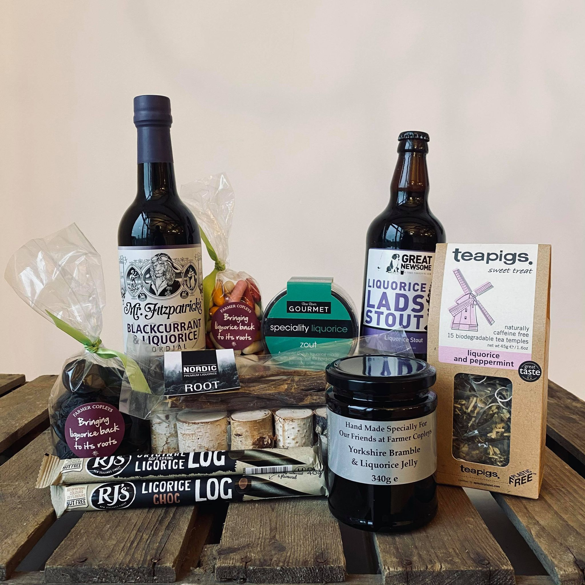 A hamper containing lots of liquorice products from Farmer Copleys on top of a wooden box