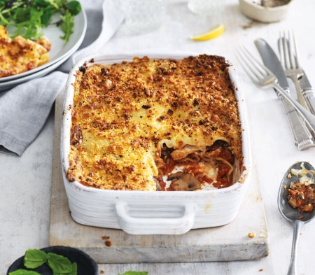 COOK Chicken & Mushroom Lasagne in a baking dish with a spoon, available for purchase at at Farmer Copleys Farm Shop